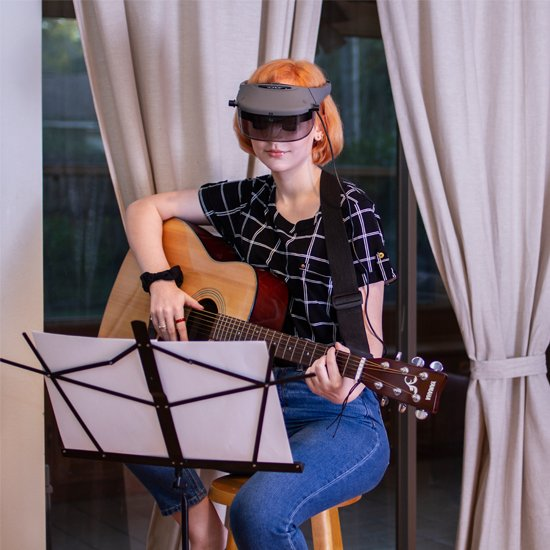 Image of a young woman playing guitar, reading music on a music stand, aided by the use of Acesight Electronic Glasses