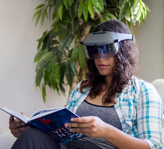 Image of a woman, seated, reading a book, aided by the Acesight unit she is wearing.